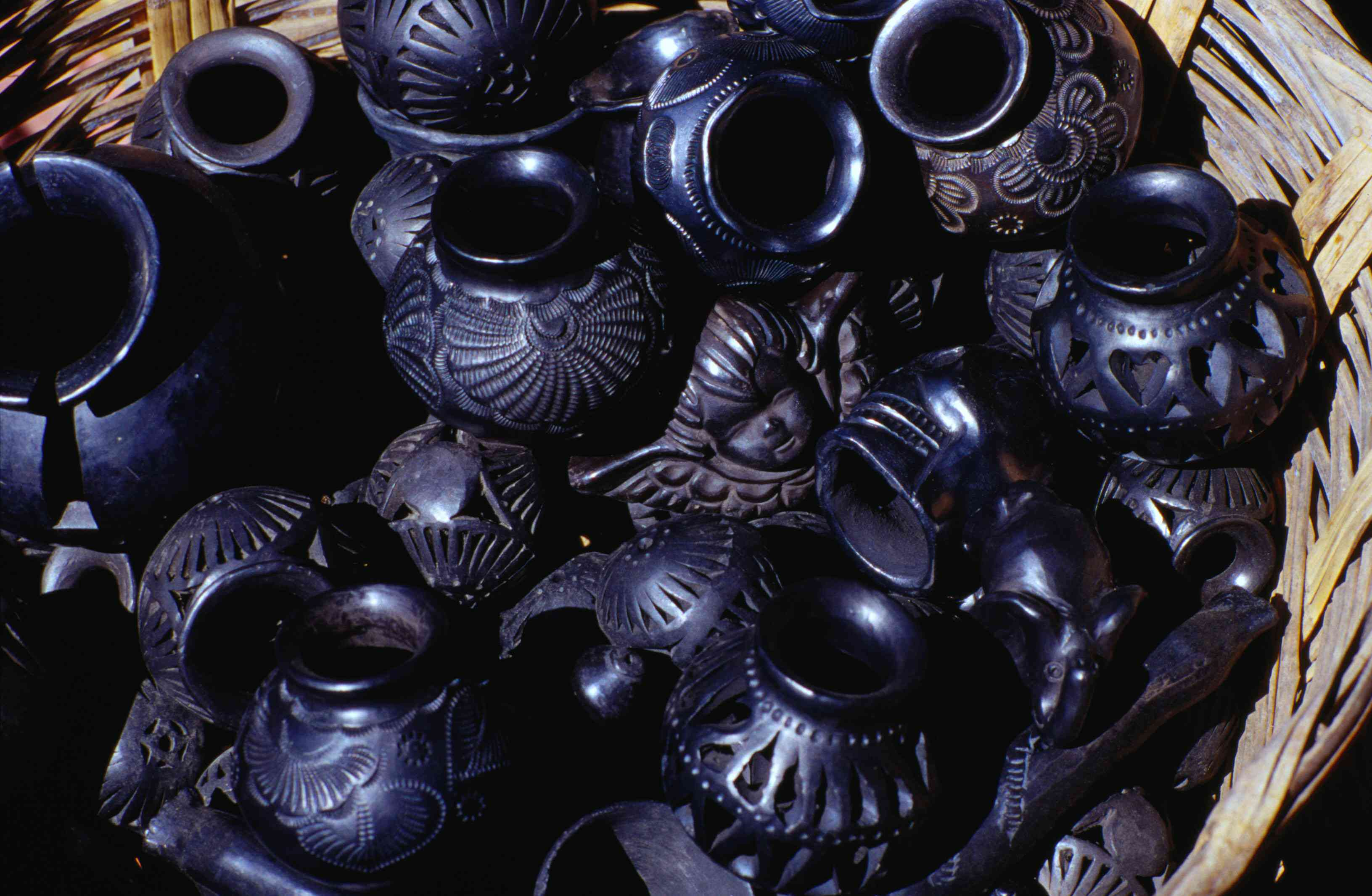 Polished black pottery in a woven pasket at the Dona Rosa workshop