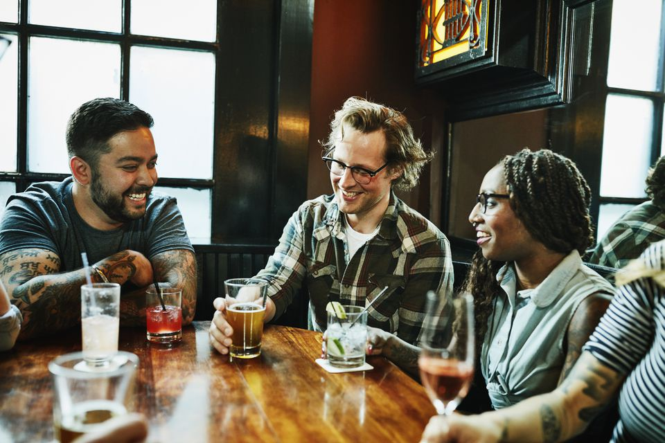 Laughing friends in discussion while sharing drinks at table in bar in Toronto