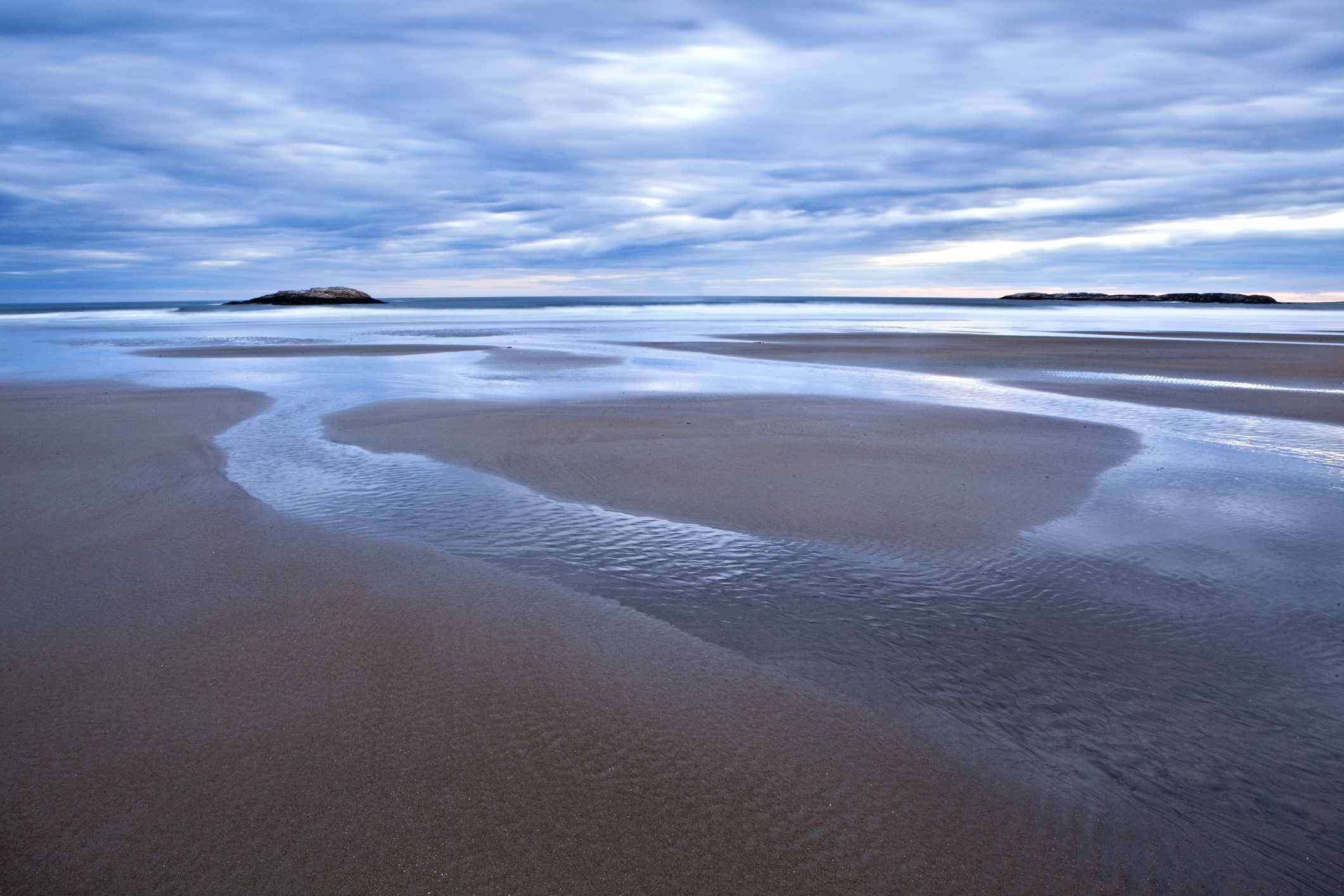 A tidal river reflects the sky along Maines Popham Beach