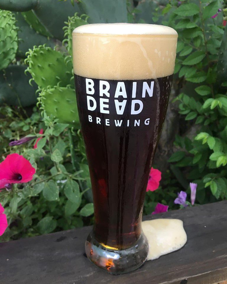 Tall glass of a dark lager with a large head overflowing out of the glass. the glass says