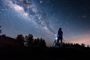 Silhouette of a man standing against a starry sky.