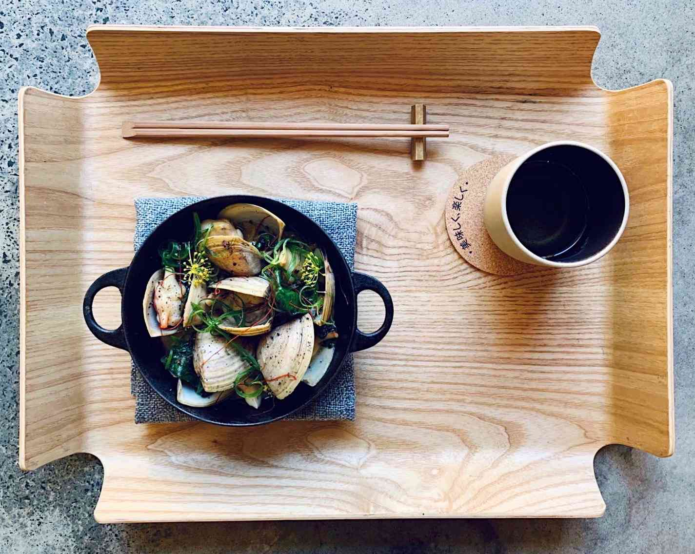 Sake-steamed clams, warrigal greens and pepperberry in black bowl on wooden tray