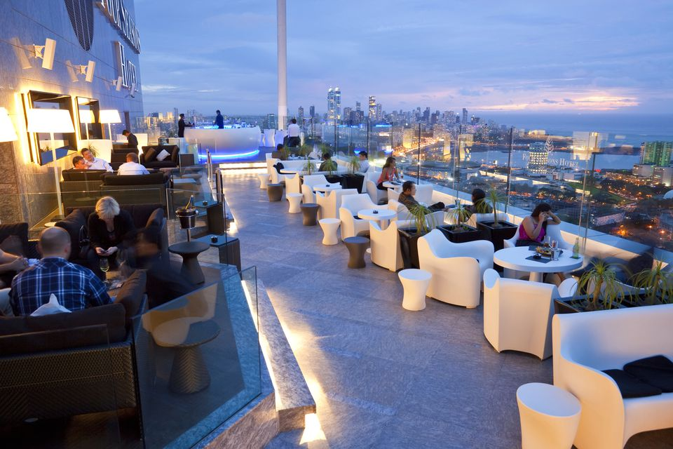 people sitting at a sleek, modern rooftop bar in Mumbai, india