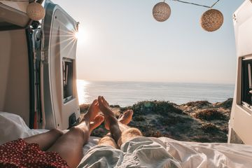 Couple lying at the back of a van looking at ocean, personal perspective