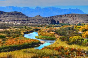creek winding through grassy plains with mountains in the background, Big Bend National Park