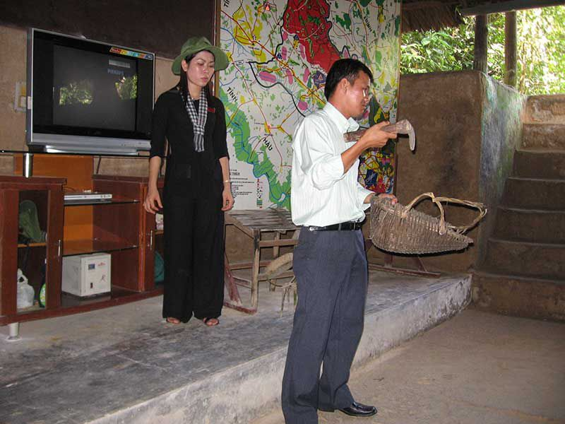Tourist displays one of the picks used to dig out the chu chi tunnels