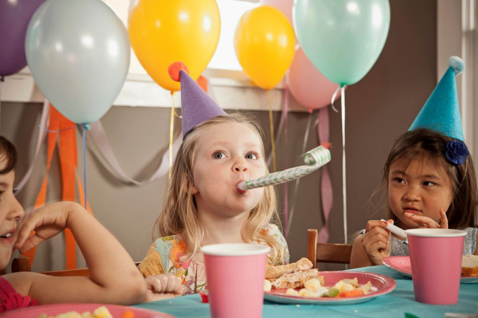 Young girl with friends at table at a birthday party