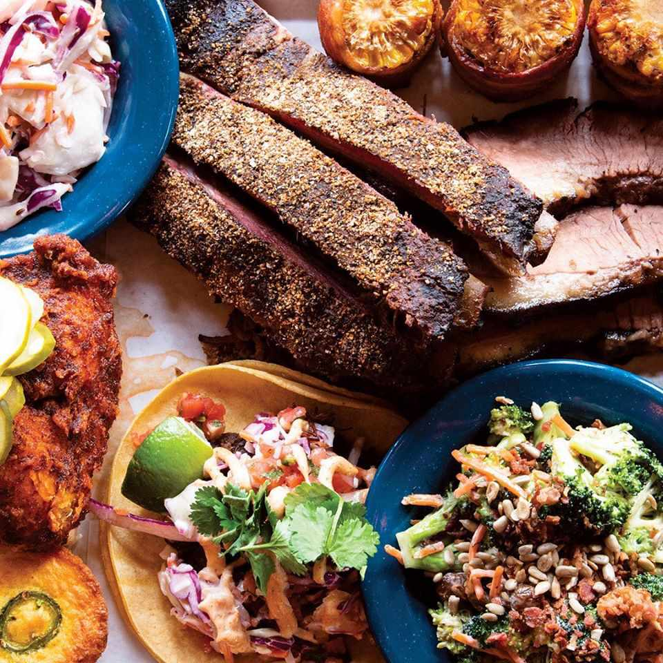 Table corwded with tacos, ribs, fried chicken, and side dishes