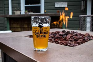 glass of beer with some sips missing on a edge of a firepit with volcanic rocks