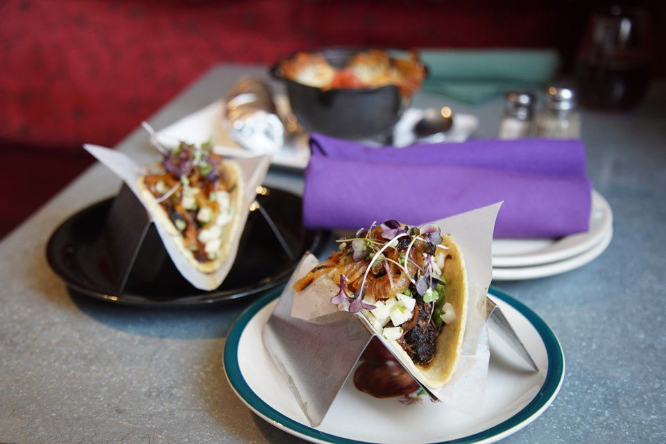 Two tacos on separate plates, one black and one white and blue.The tacos have white onions, caramelize onions, braised meat and cilantro. Behind one taco and to the right of the other are two white plates stacked on top of each other with two rolled, purple napkins sitting on top