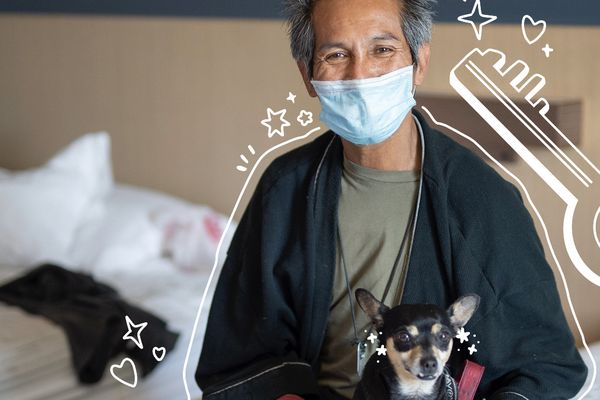 A man with his dog in a hotel room with an illustrated key around them