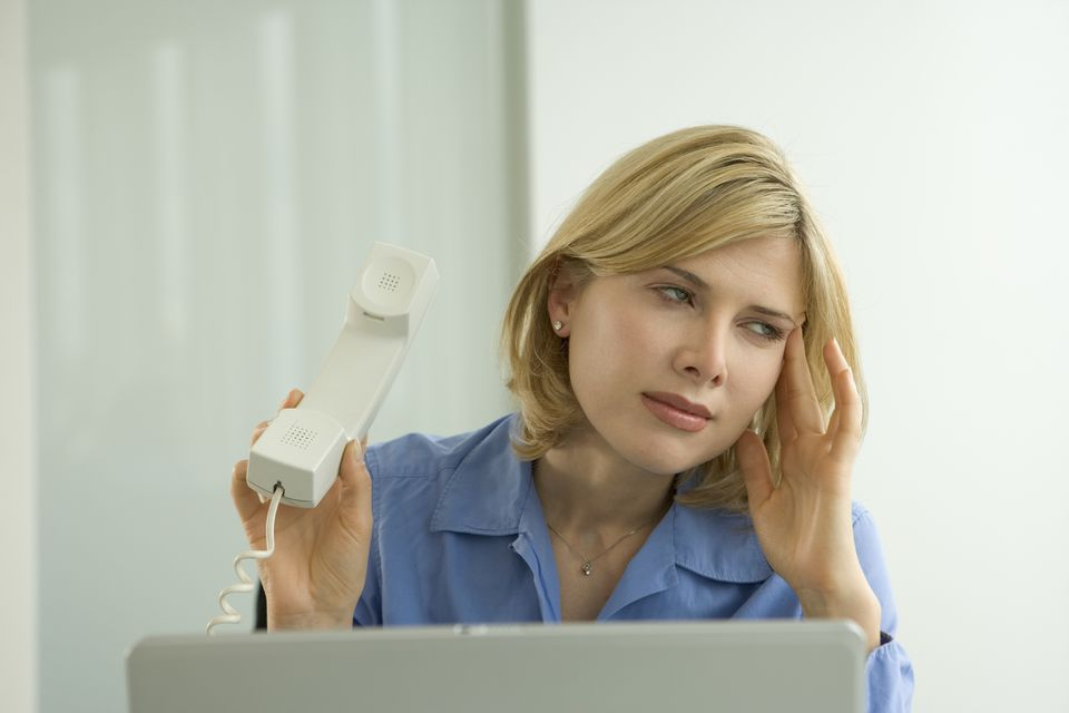 Businesswoman at desk holding phone away from ear