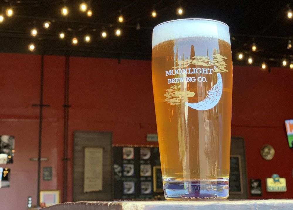 Light colored beer in a pint glass that reads