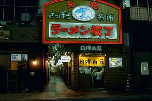 alley of restaurants with a large sign in japanesese over the alleys