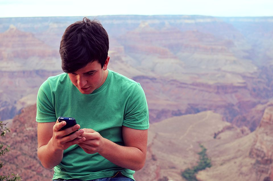 Teenager using cell phone at Grand Canyon