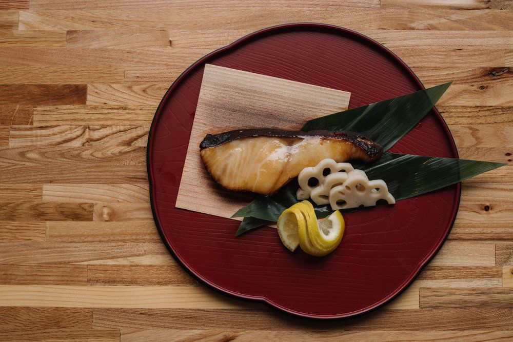 Grilled black cod with two, cut bamboo leaves, three half-slices of lotus root and lemon sliceson a red, wooden plate