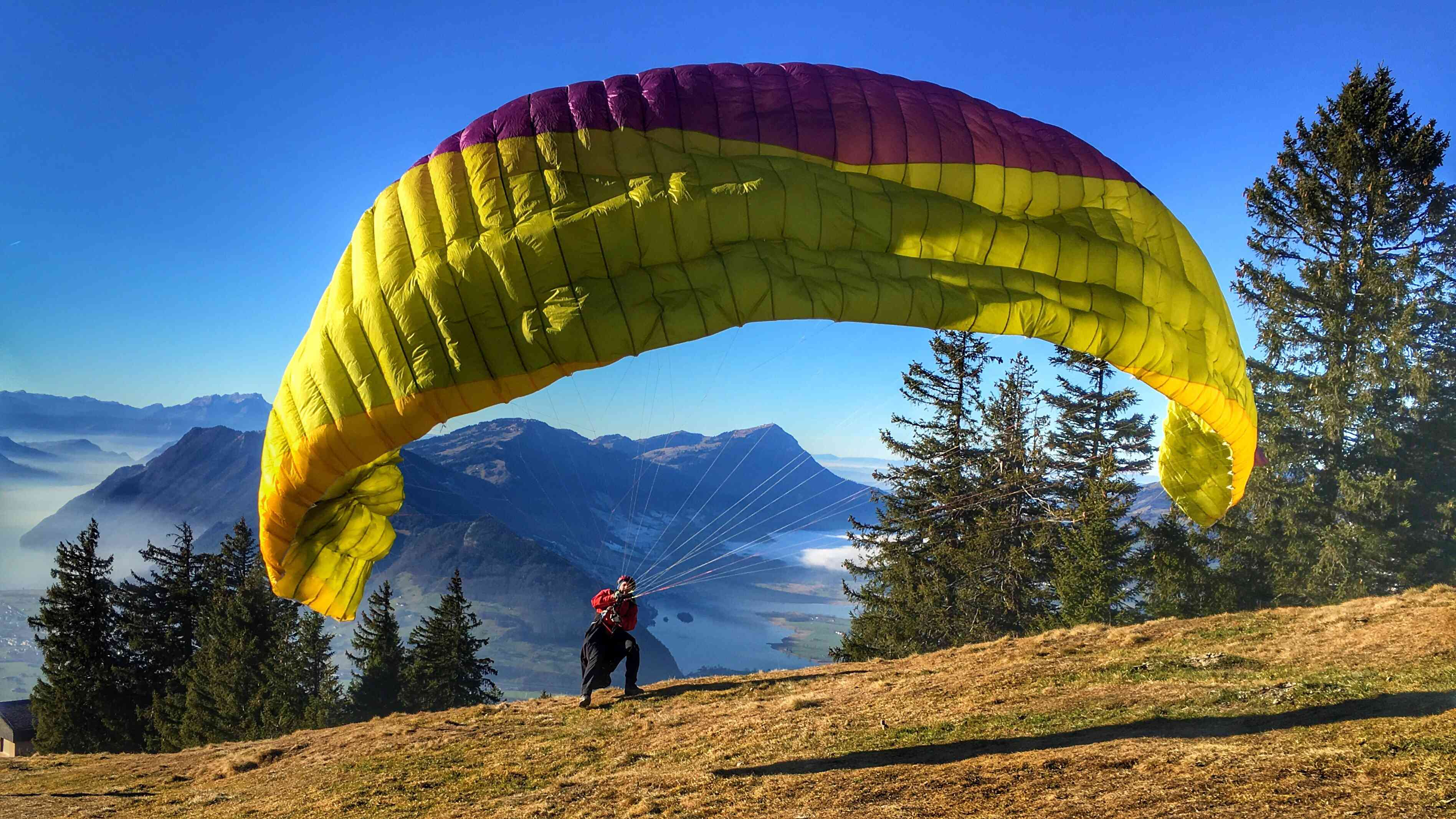 large yellow parasail about to take off with trees and mountains in background
