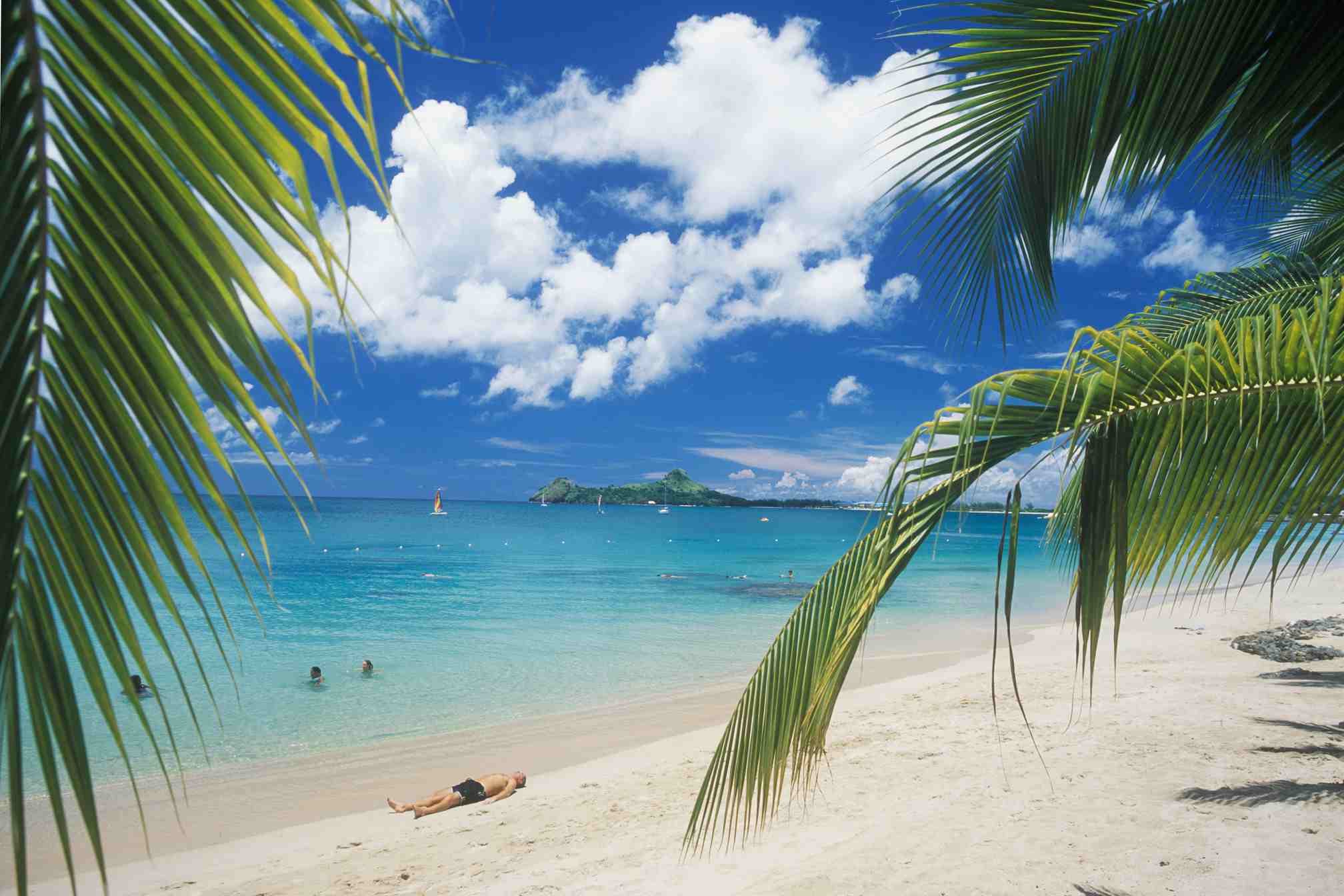 People swimming and sunbathing on Reduit Beach in St. Lucia