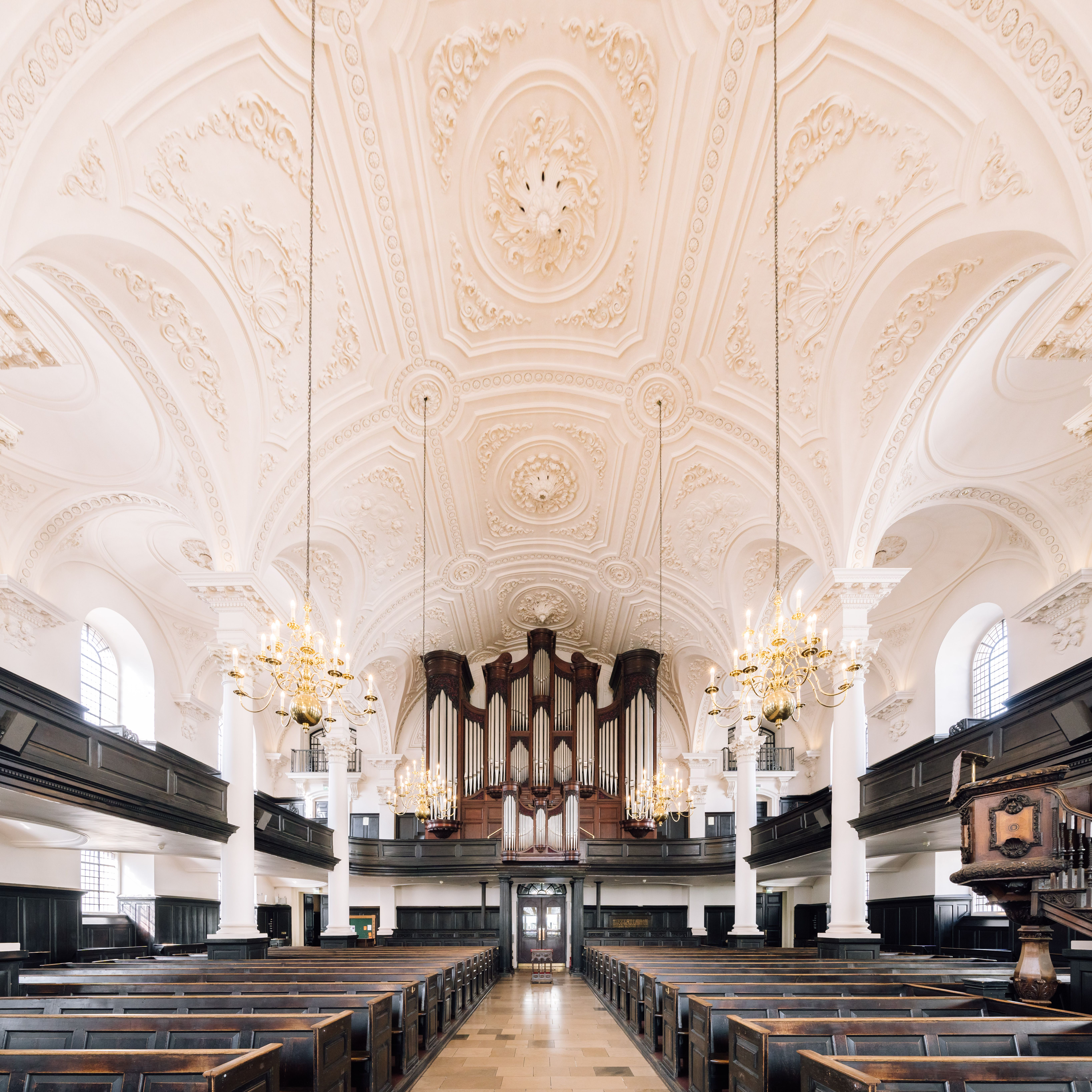 Interior of St. Martin-in-the-fields with dark brown pews and a white domed ceiling