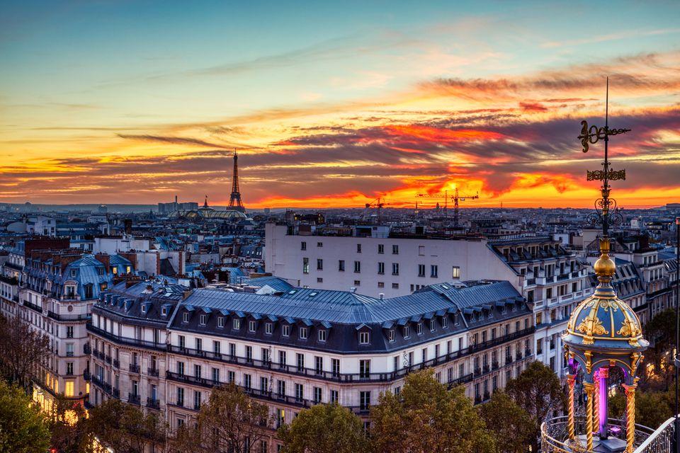 Vista aérea de París iluminada al anochecer con la Torre Eiffel