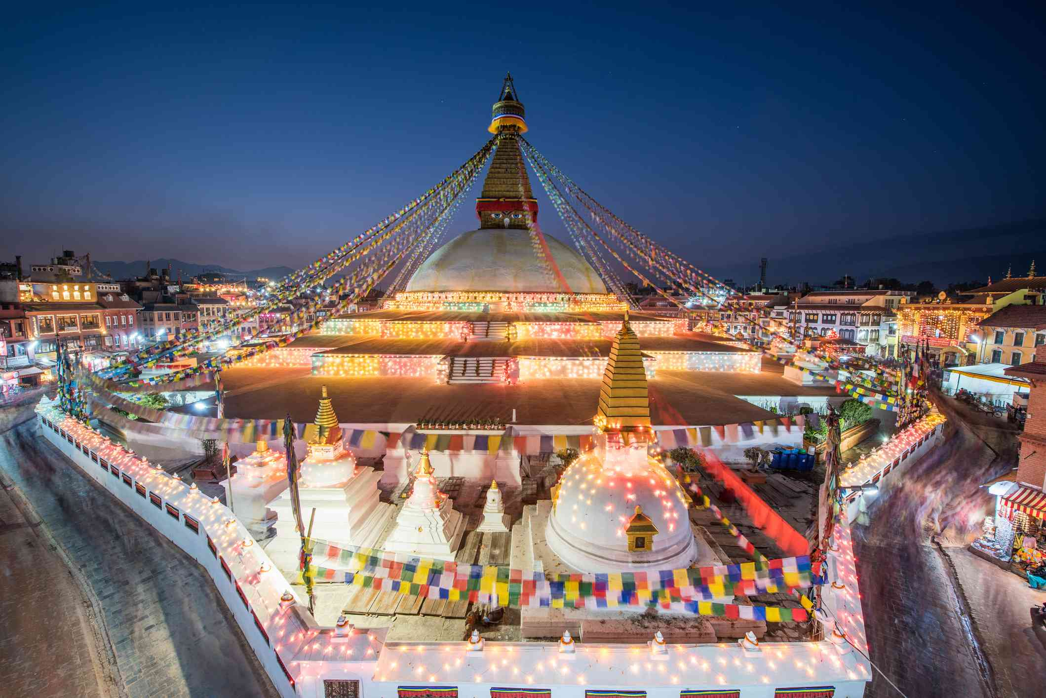 tall Buddhist stupa strung with flags and lit up at night