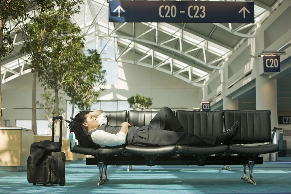 Businessman resting on chairs in airport
