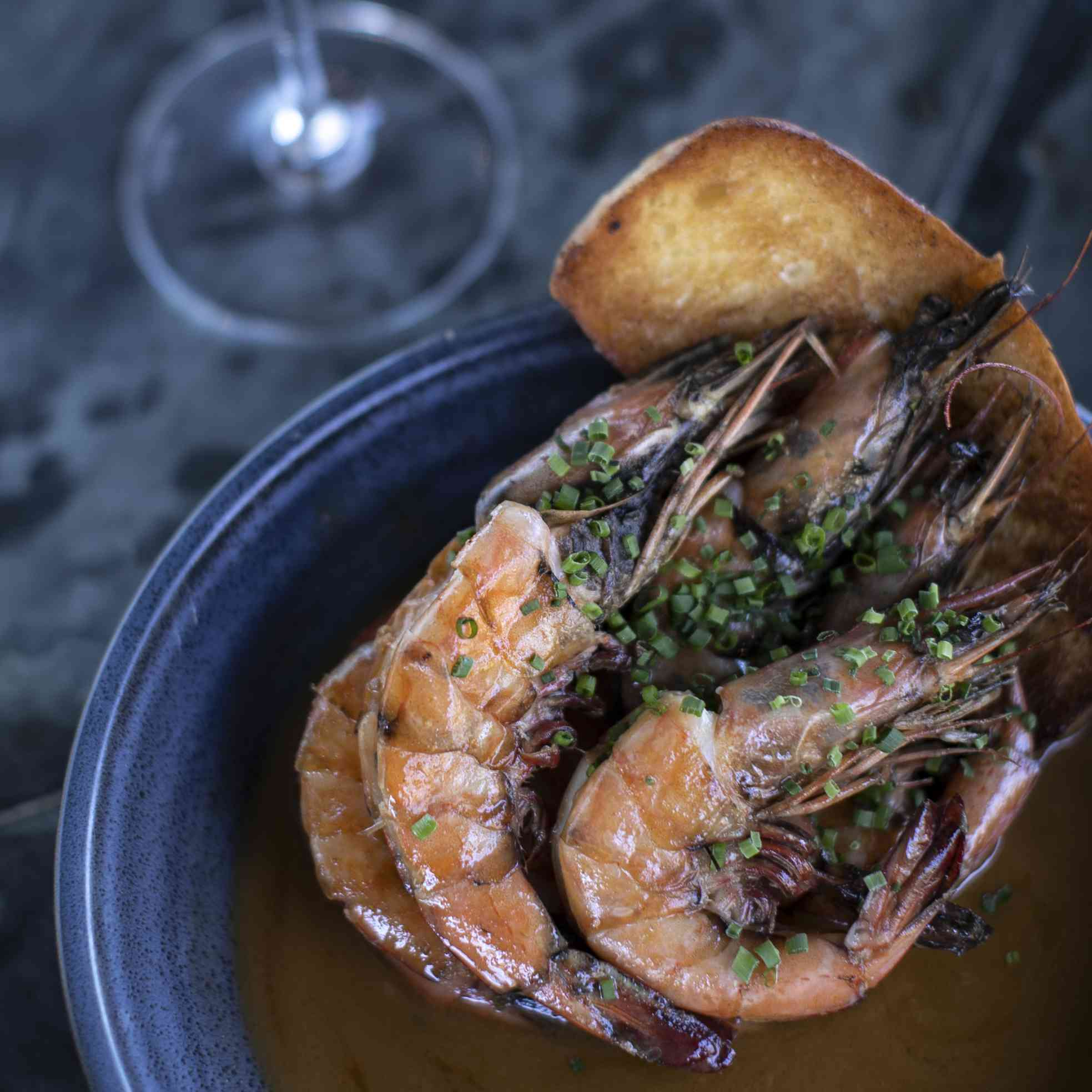 Barbecued white shrimp in a blue bow with a brown sauce