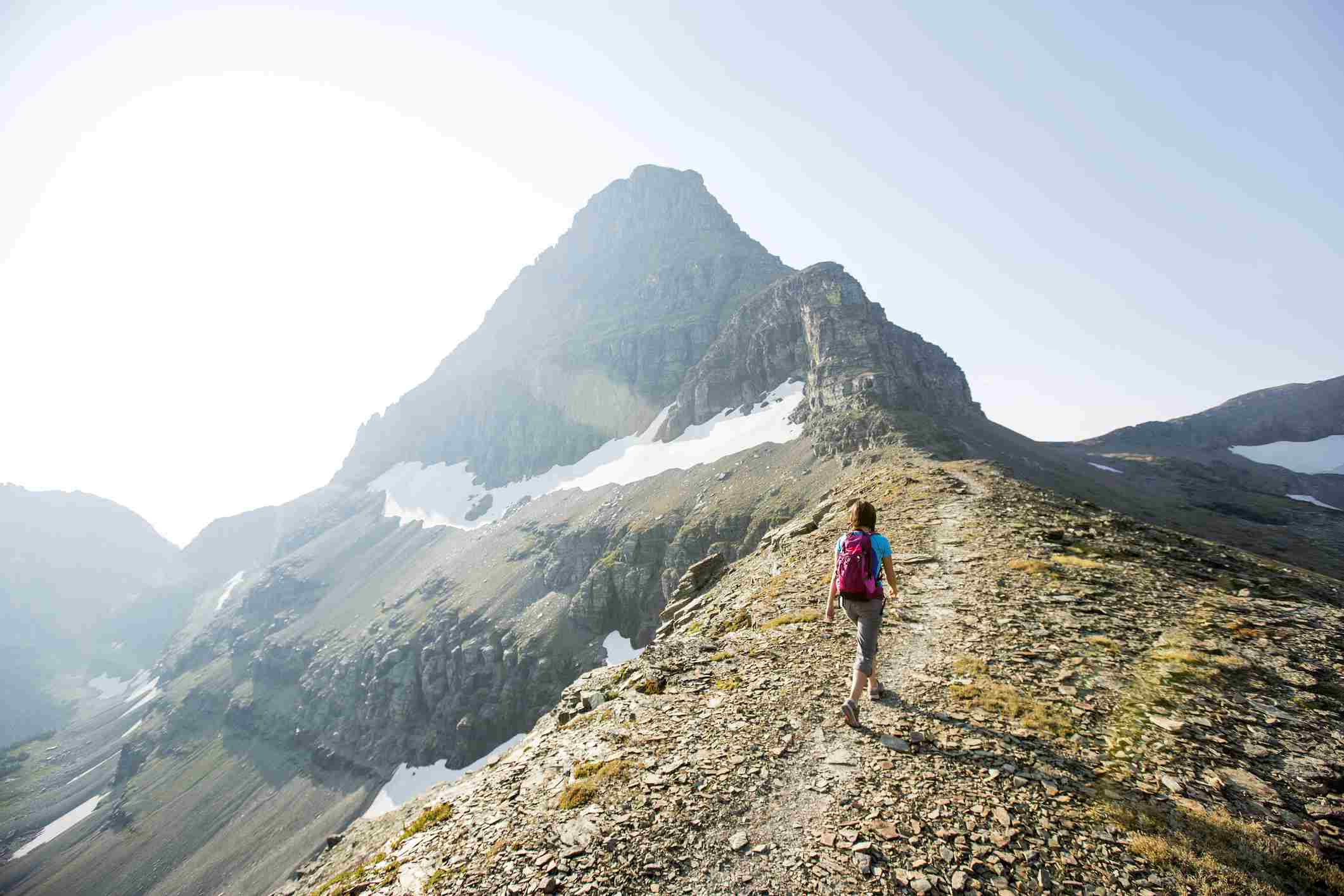 A woman hiking a scenic trail in Glacier National Park.