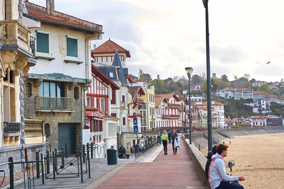 The typical colorful beachfront architecture of the beautiful Basque town Saint Jean de Luz, with people strolling on the seafront