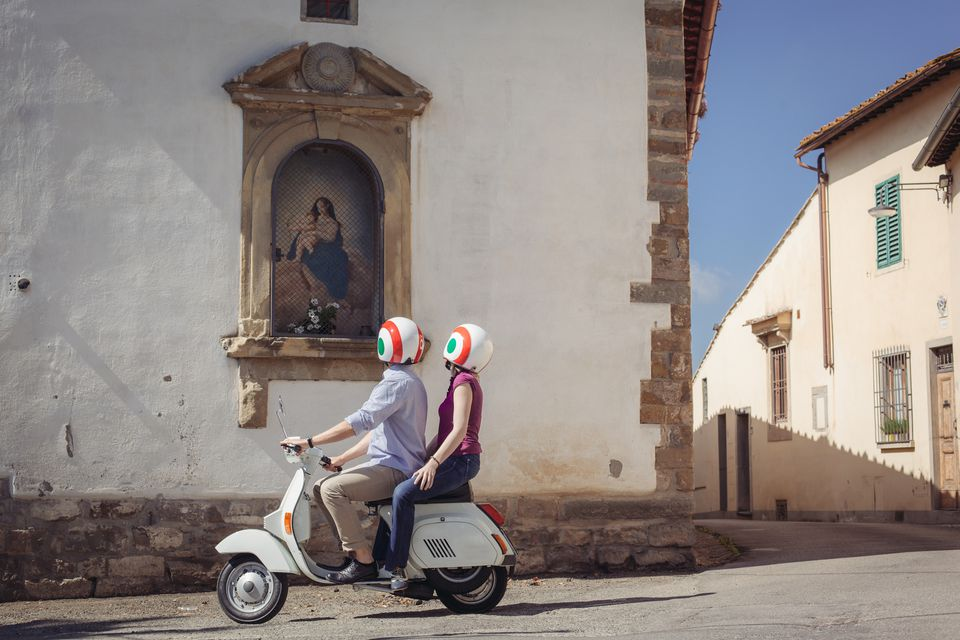 Couple looking at church painting from moped, Florence, Italy