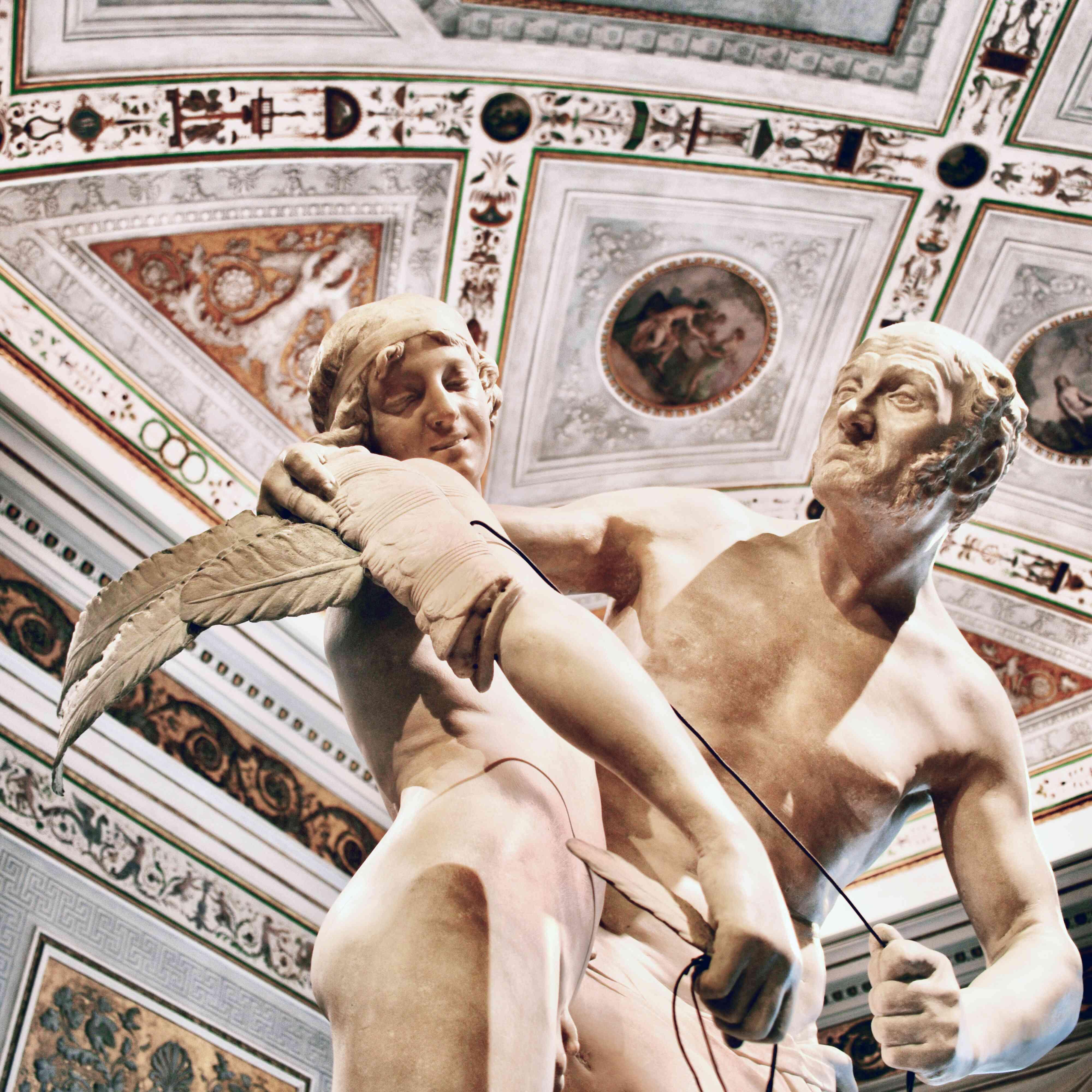 Una estatua de mármol con un detallado techo pintado en el Museo Cívico