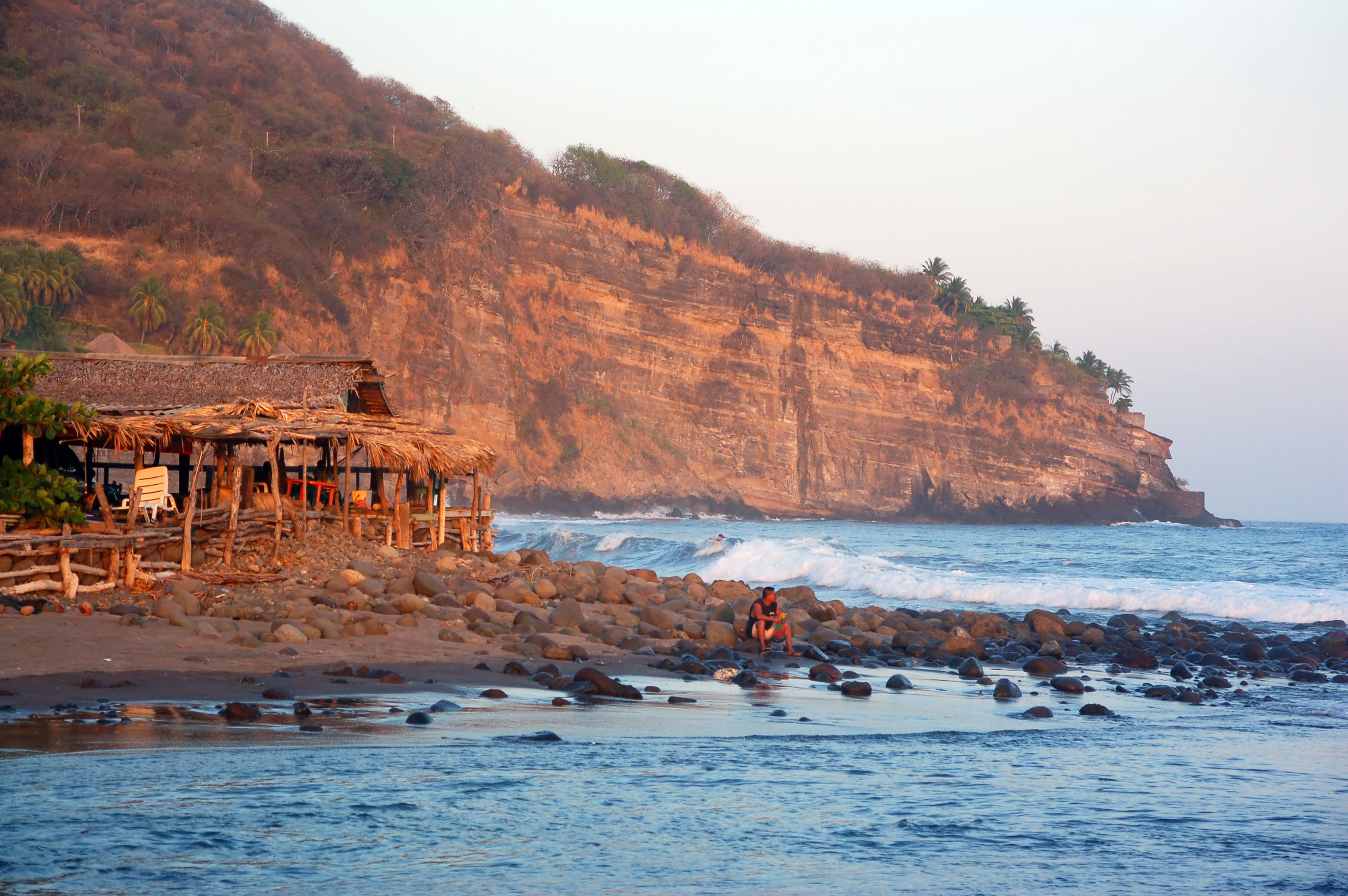 Man enjoying a peaceful afternoon on rocky beach of Playa El Zonte.