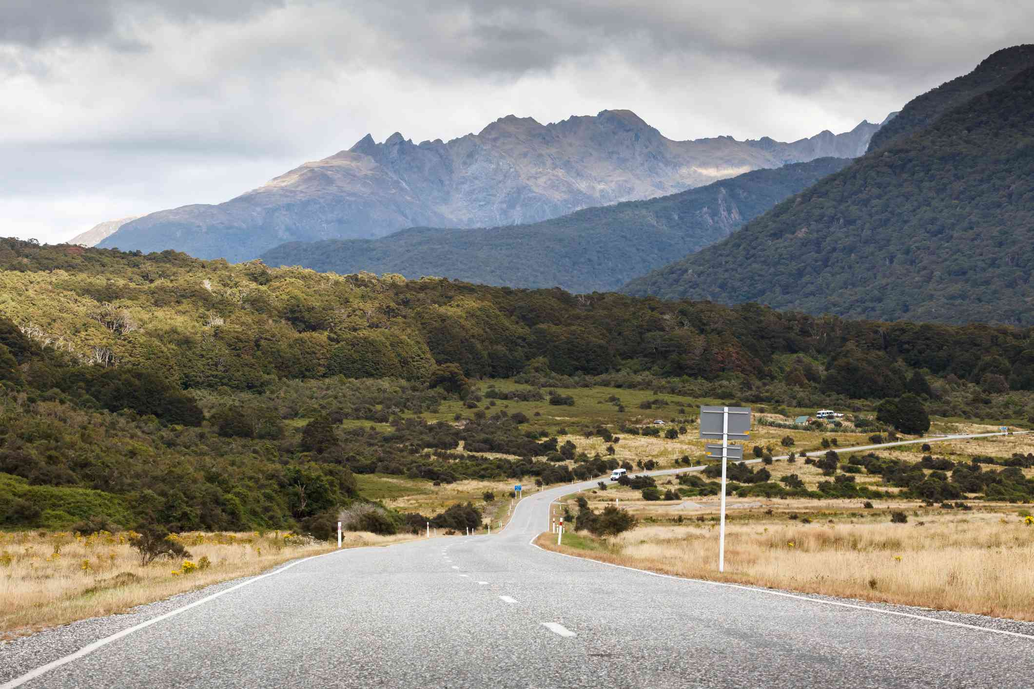 mountains with a two-lane road leading towards it