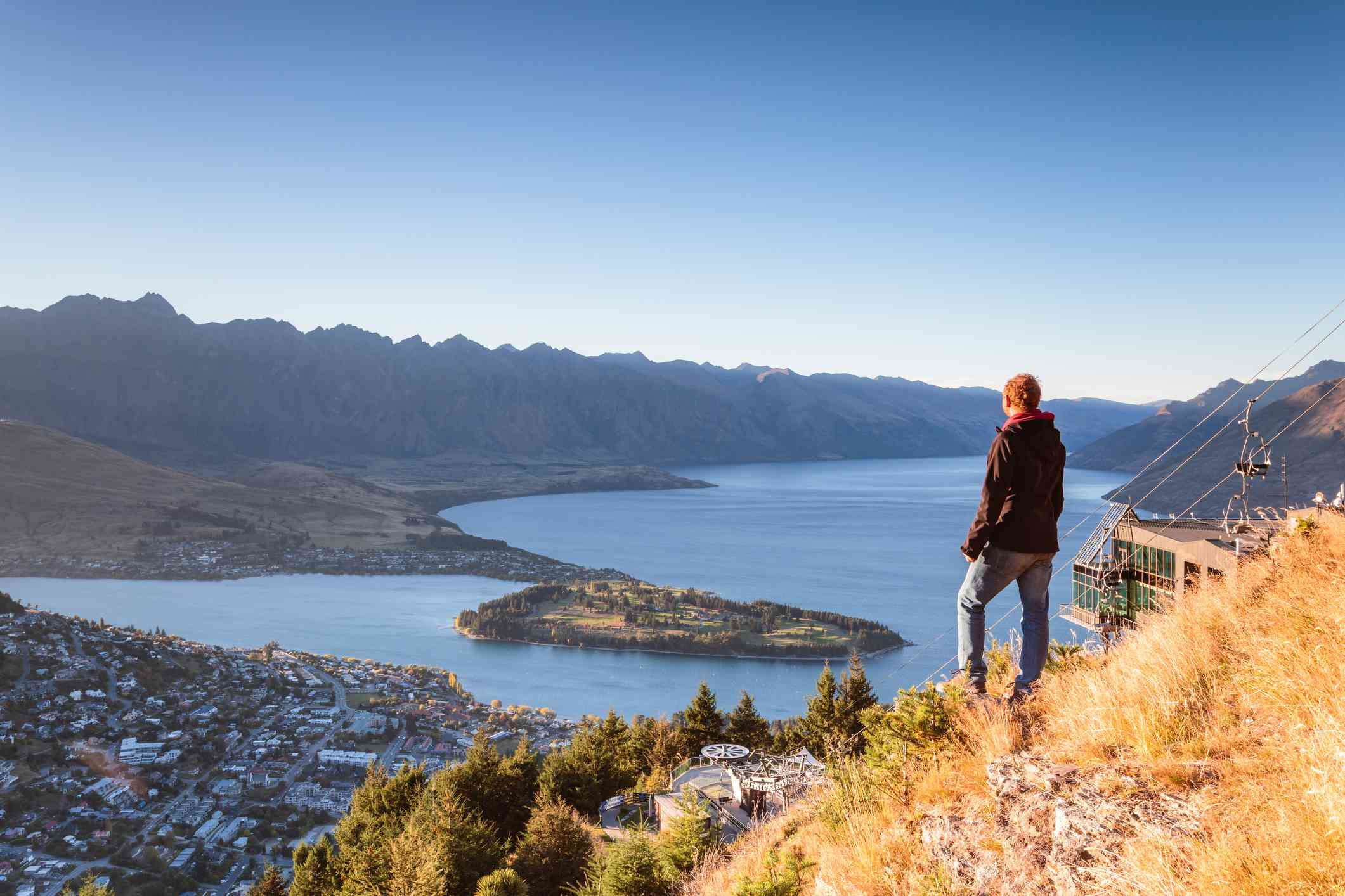 man on grassy ledge high on a hill overlooking a town, lake and mountains