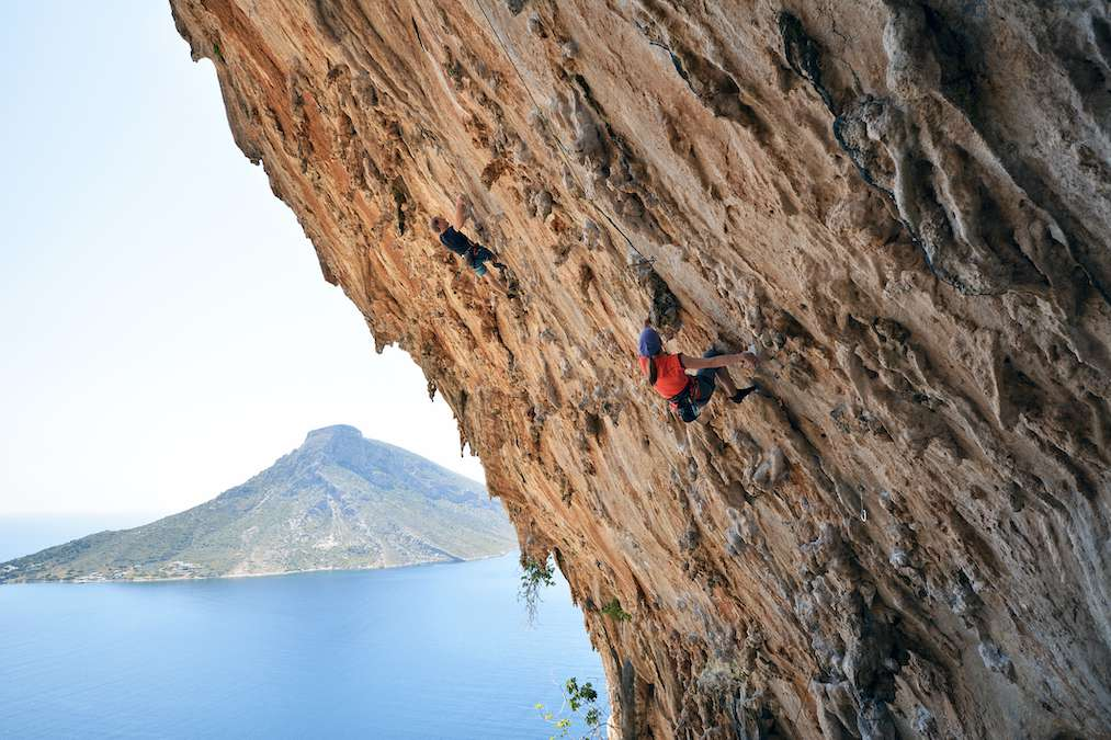 A rock climber clinks to a cliff with a volcano in the background.