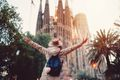 Rear view of young woman in front of Sagrada Familia with arms outstretched
