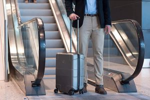 Man holding Victorinox Lexicon Hardside Frequent Flyer 8-Wheel