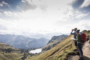 Germany, two backpackers with map and binoculars in alpine scenery