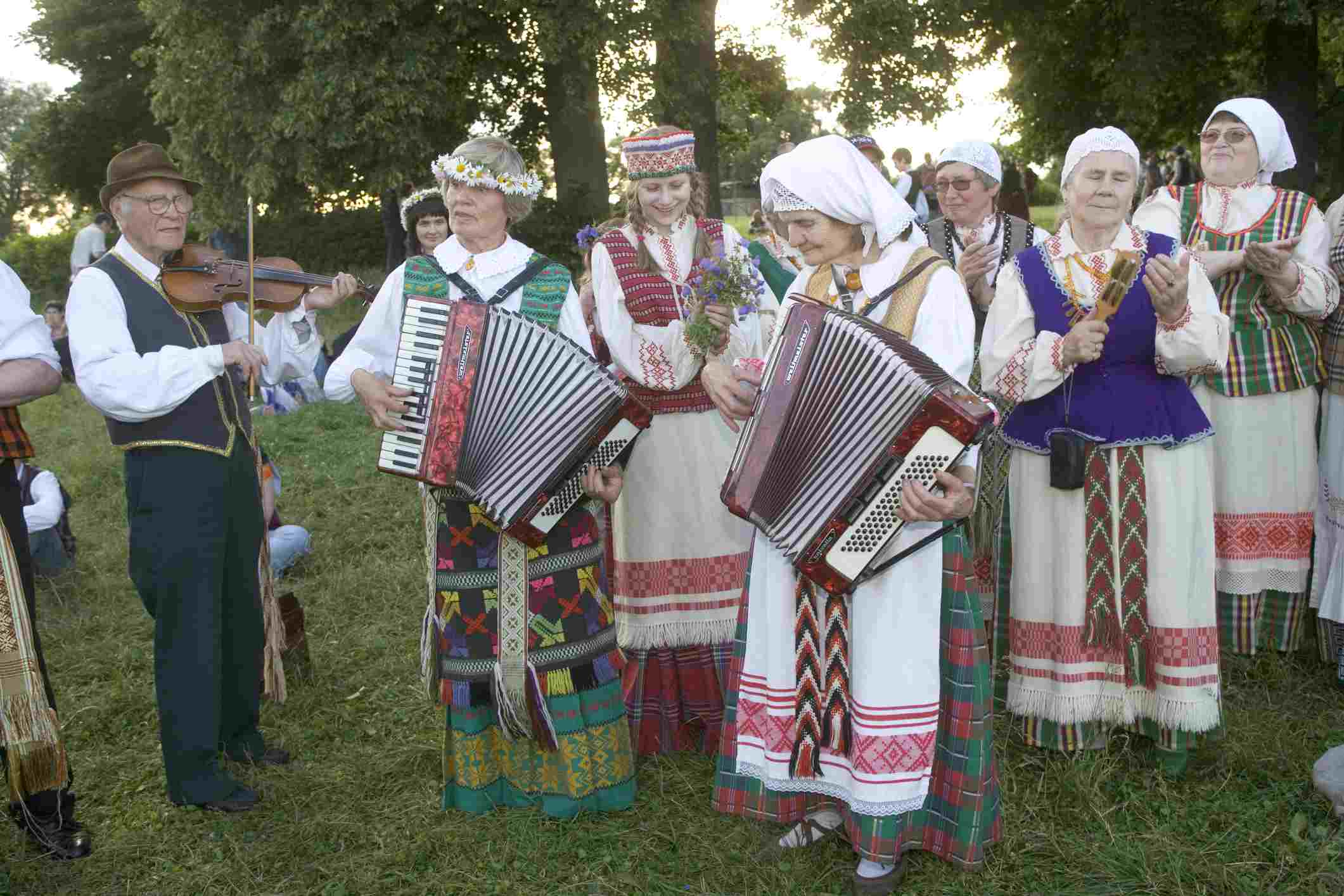 Men and woman in traditional dress playing instruments at the Midsummer's Day Celebration