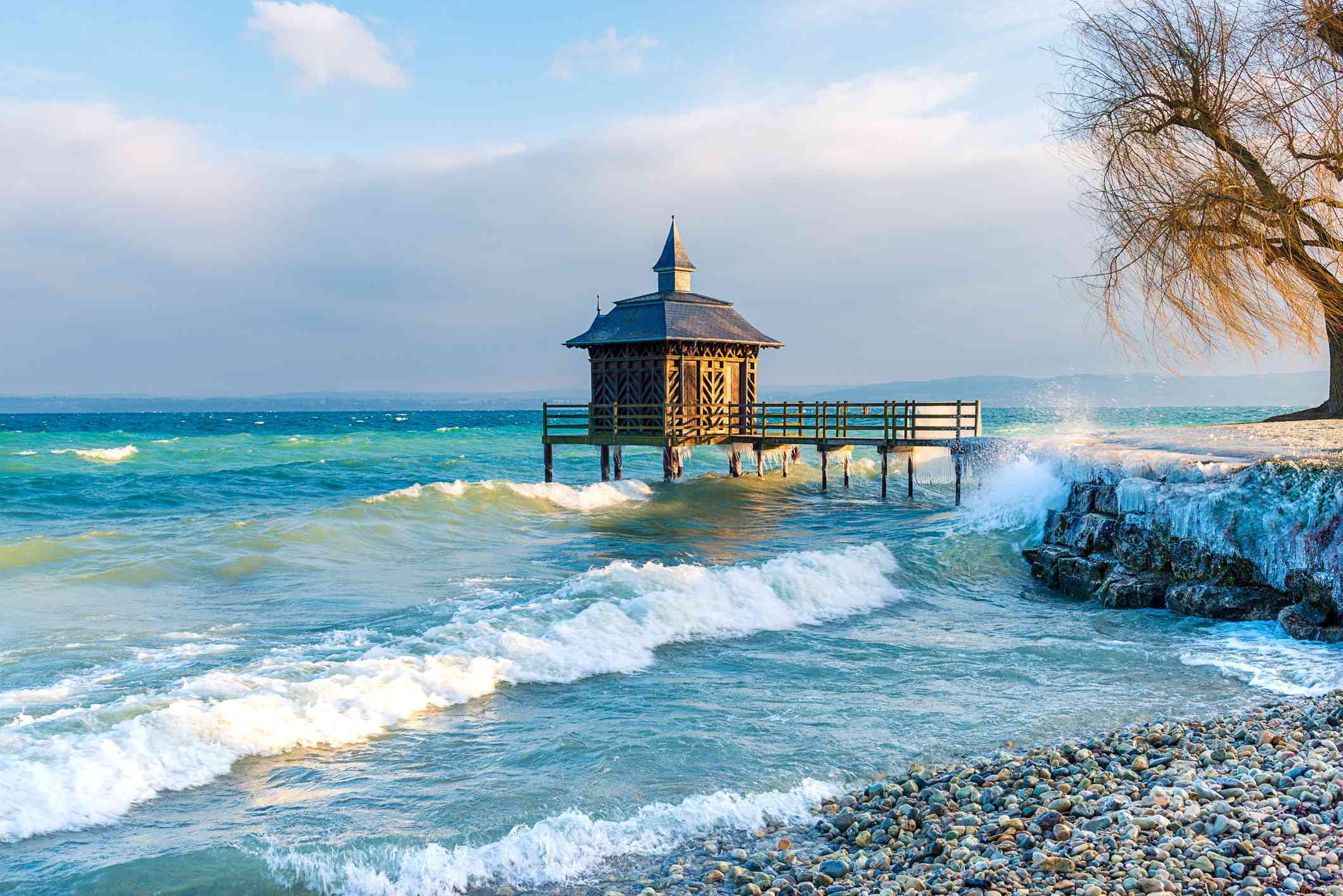 waves crashing against the rock shore of Lake Neuchatel in winter. There is short boardwalk with a small building at the end