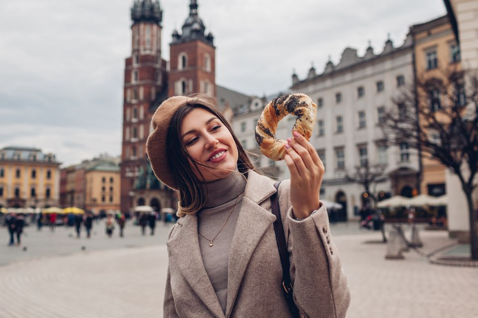 Tourist woman eats bagel obwarzanek traditional polish cuisine snack on Market square in Krakow. Travel Europe