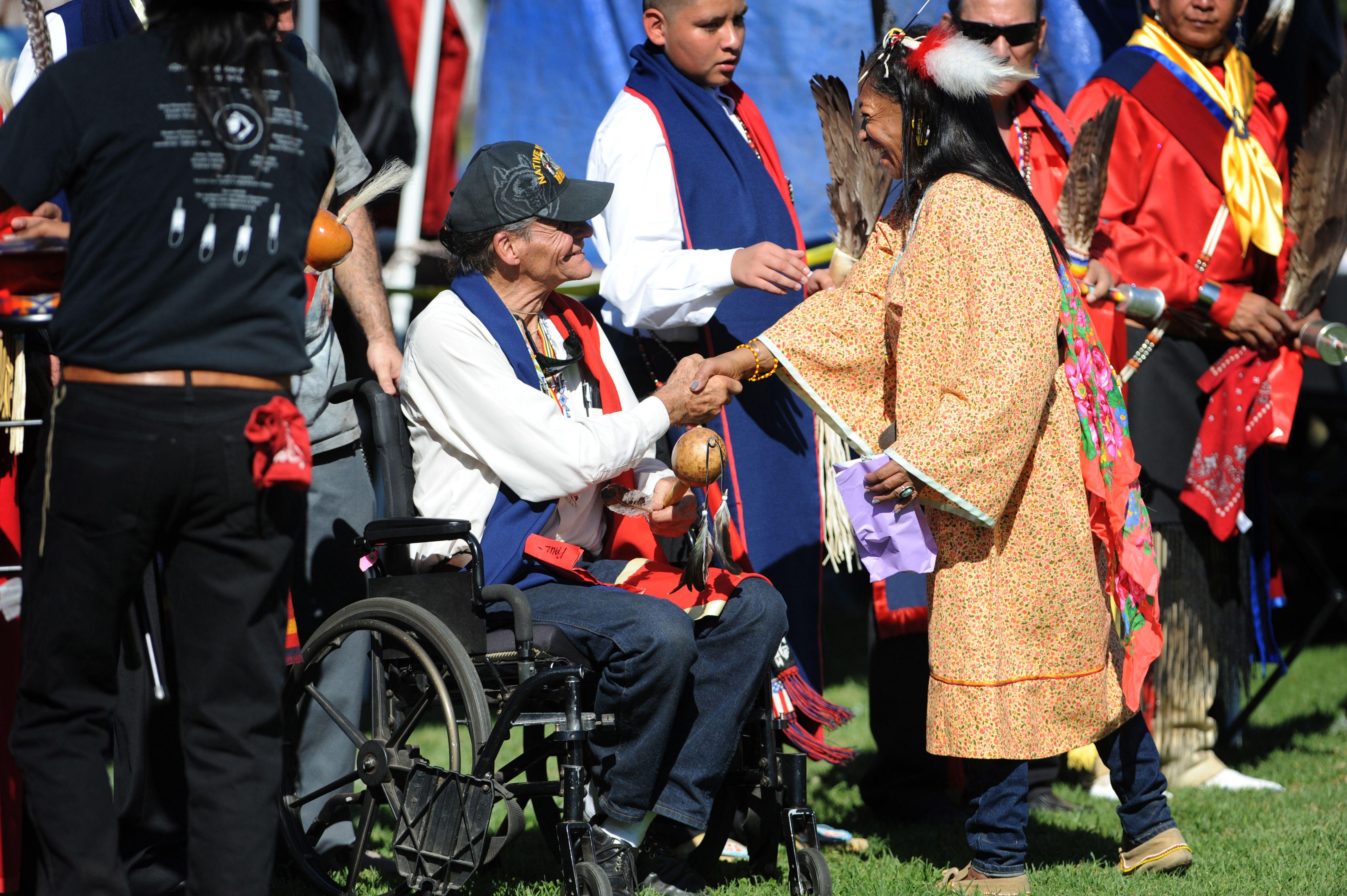 Tribe member greets Navy World War II veteran Paul Duronslet, a Cherokee tribesman from Los Angeles, Calif., during the gourd dancing festivities at Native American Veterans Association's Annual Veterans Appreciation