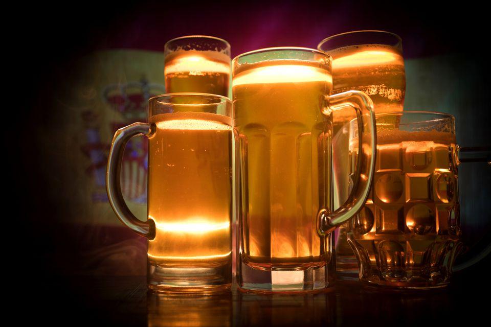 Una colección de vasos de cerveza ante una bandera española