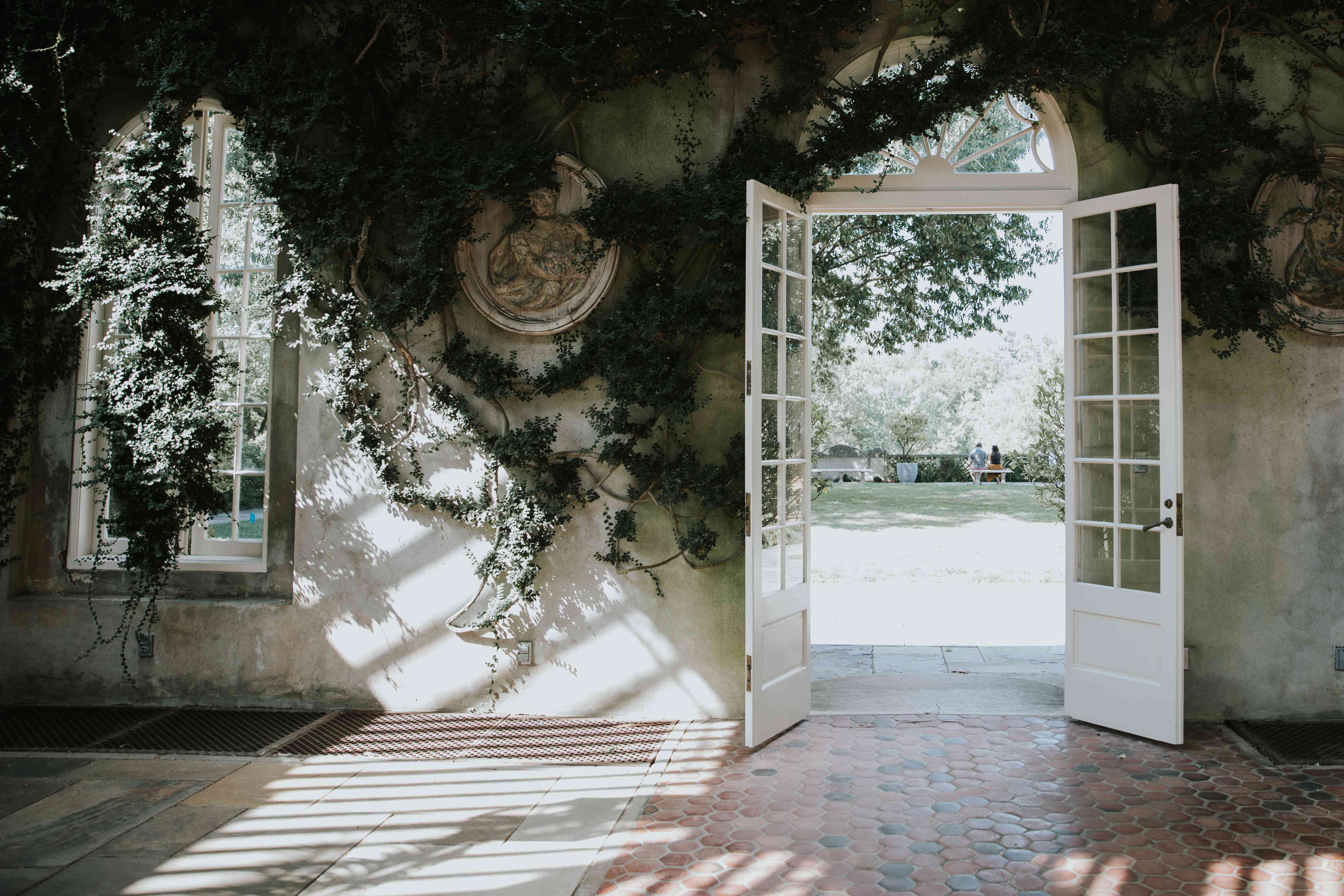 A wall covered in vines with a white door opening to a garden in Dumbarton Oaks