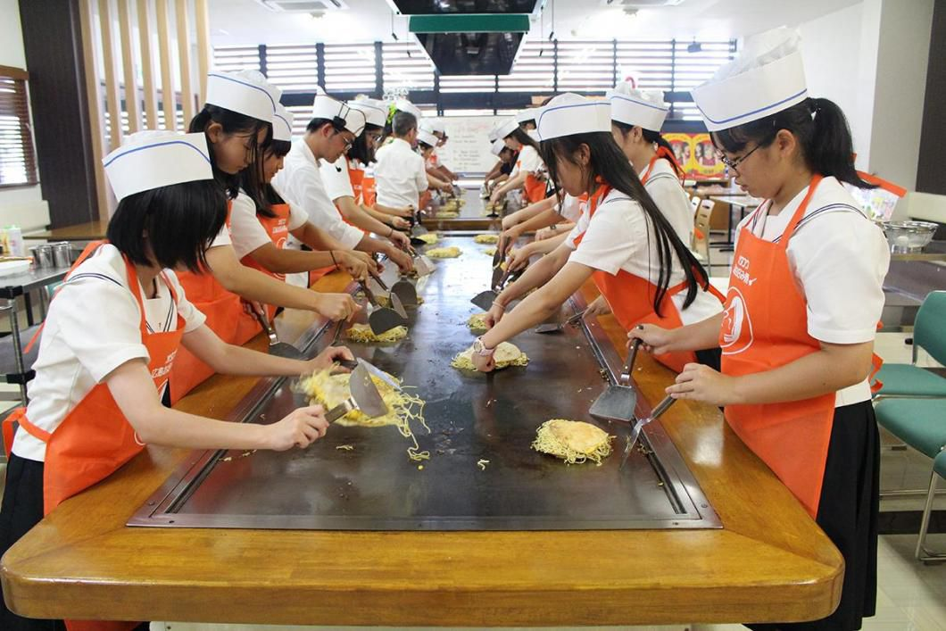 group of japanese students in aprons and paper hats making okonomiyaki on a griddle