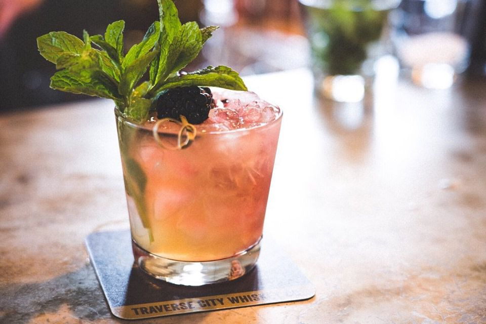 Pink and orange alcoholic drink with ice, a sprig of mint and a blackberry from Traverse City Whiskey Co.