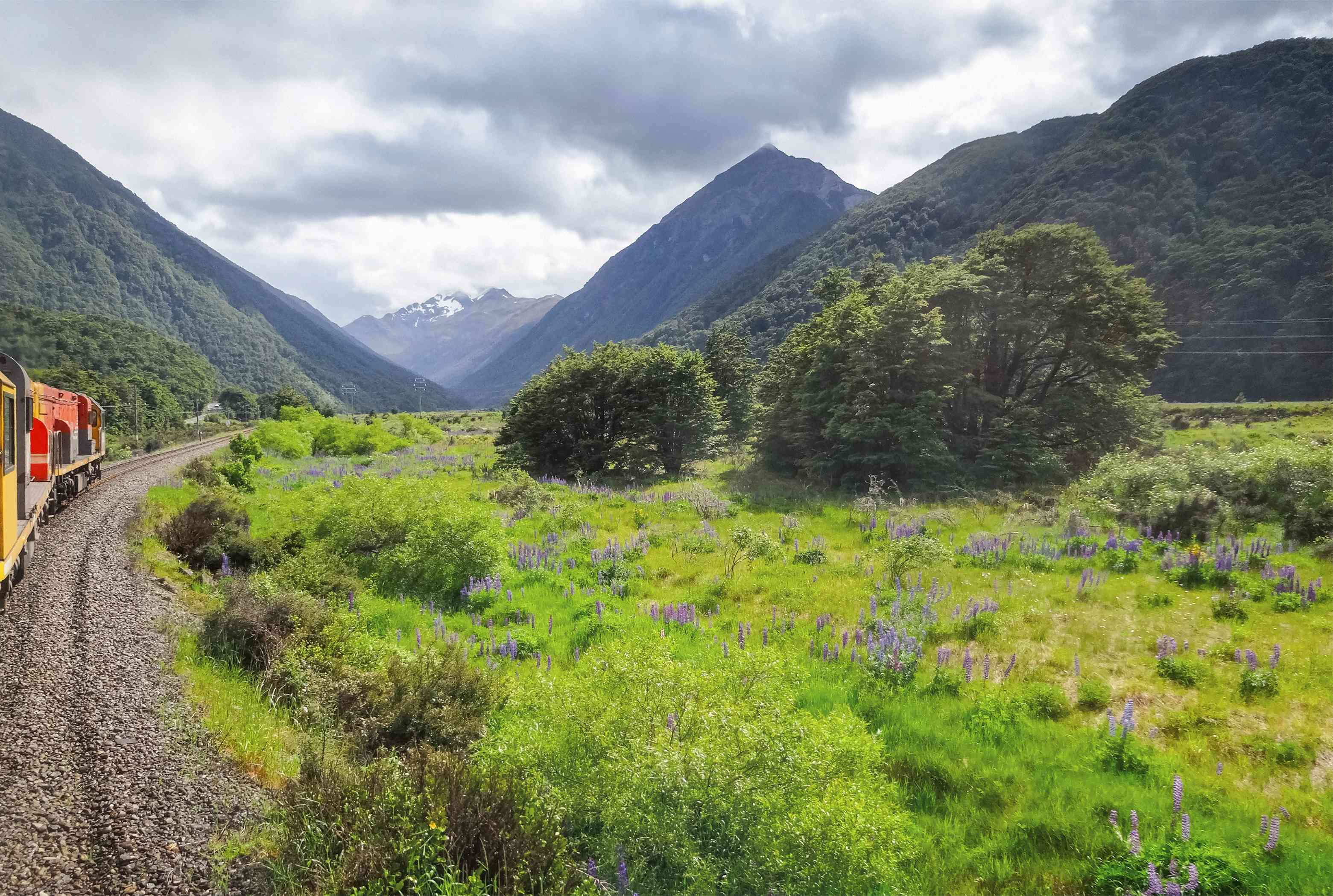View of mountains and grassy fields from them Tranzalpine Railway and train on South Island New Zealand