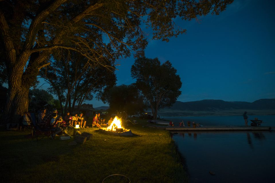 Family hanging out around a campfire by a lake in Ennis, Montana