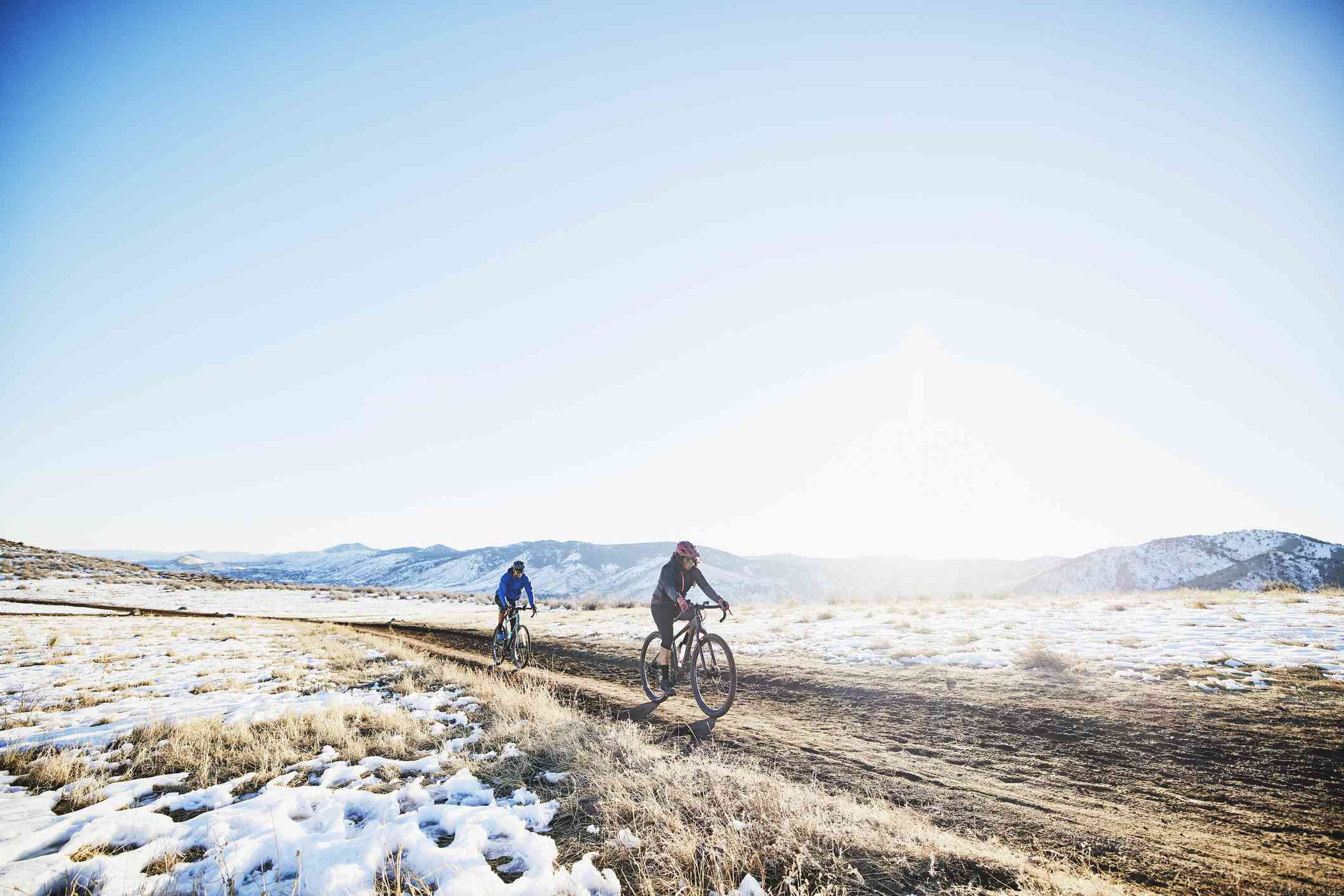 Friends riding gravel bikes up hill on dirt road on winter afternoon