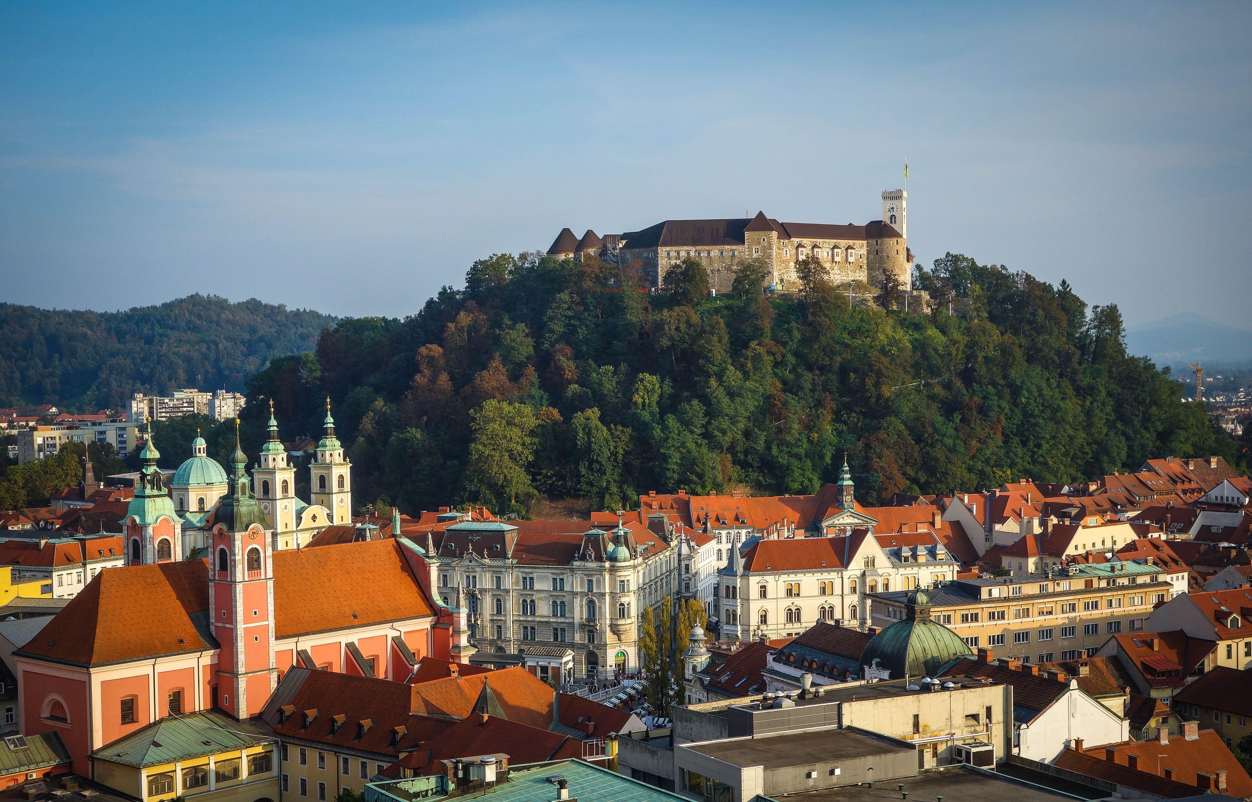 Eslovenia, Ljubljana, Castillo en la colina boscosa y paisaje urbano circundante